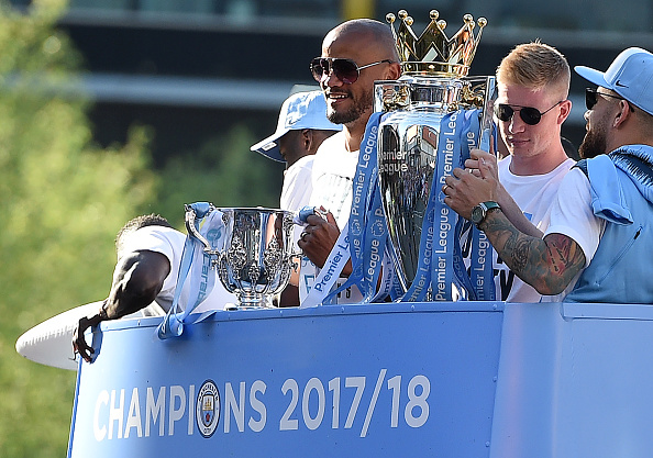 Manchester City's Belgian midfielder Kevin De Bruyne (2R) holds up the Preimer Leagu trophy as Manchester City's Belgian defender Vincent Kompany (C) holds up the English League Cup trophy to fans as the Manchester City team take part in an open-top bus parade through Manchester, northern England on May 14, 2018 to celebrate winning the 2018 Premier League title. - Manchester City set the seal on a record-breaking season by becoming the first side in English top flight history to hit 100 points with victory at Southampton on Sunday. City also added another landmark by winning the league by a record 19 points from local rivals Manchester United. (Photo by Oli SCARFF / AFP) (Photo credit should read OLI SCARFF/AFP/Getty Images)